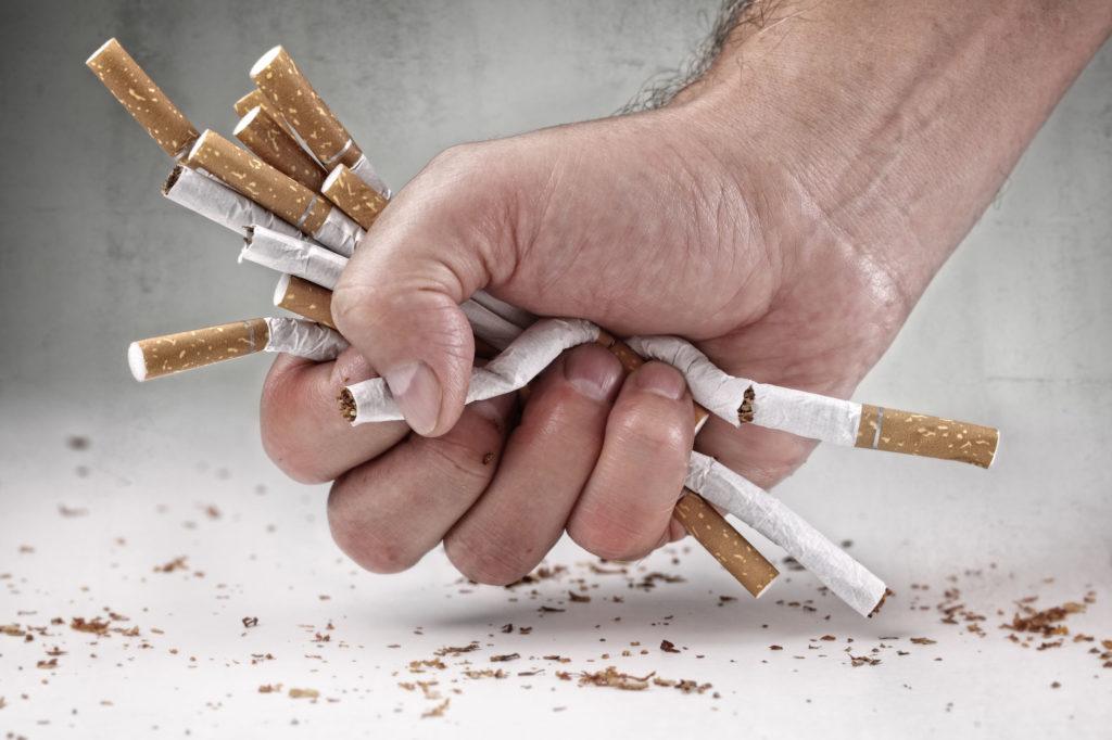 Mão amassando cigarros simbolizando o ato de parar de fumar