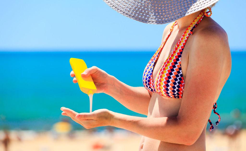 Mulher passando protetor solar na praia