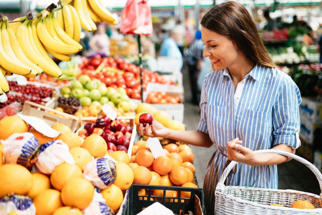 Mulher escolhendo frutas no mercado